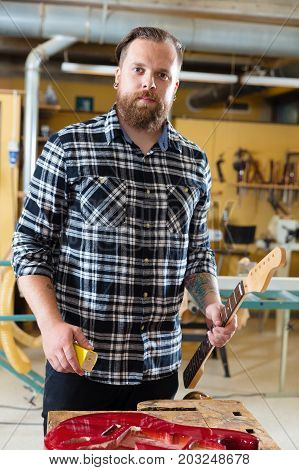 Craftsman work on a guitar neck in a workshop for wood. Hard working man with tattoo and beard working with musical instruments.