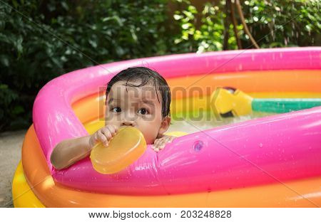 Baby boy play water in kiddie pool by alone