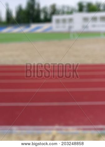Close-up picture of a blurred running track in the sports stadium. A bright red track for running trainings and competitions as a background. Sports, outdoors, summer concept. Copy space.