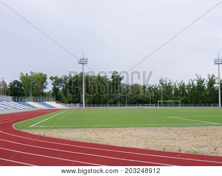 A summer stadium with a football field and a red track for running trainings and competitions on a green natural background. Sports, outdoors, summer, football concept. Copy space.