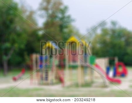 Bright blurred playground as a background. A colorful playground equipment for children's active pastime in the park. Red slides. Outdoors, sports, childhood concept. Copy space.
