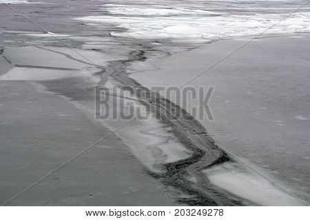 A crack forms on the thinning ice covering Little Traverse Bay, near Wequetonsing, Michigan, during March.