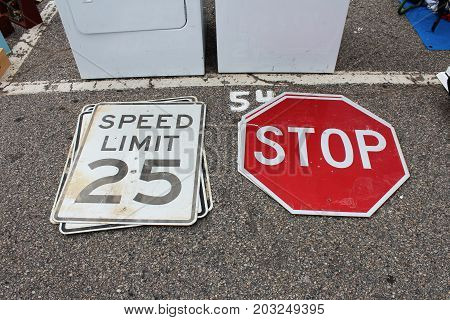 Speed limit and stop signs at an outdoor flea market
