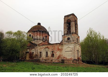 brick ruins of old ancient orthodox chrurch with bell tower in meadow with green grass and trees