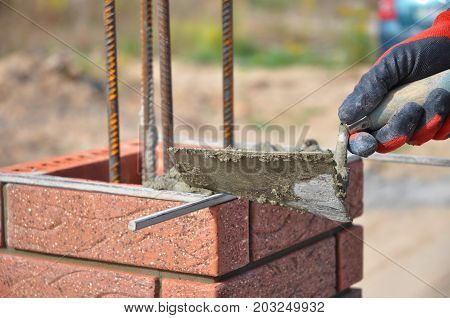 Bricklaying closeup. Bricklayer hand holding a putty knife and building a brick fence column. Building brick.
