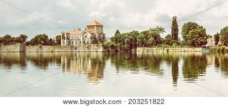 Beautiful castle with greenery and cloudy sky in Tata Hungary. Architectural theme. Fortress is reflected in the lake. Photo filter.