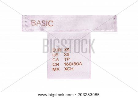 Pink textile clothes label lettered basic on white background