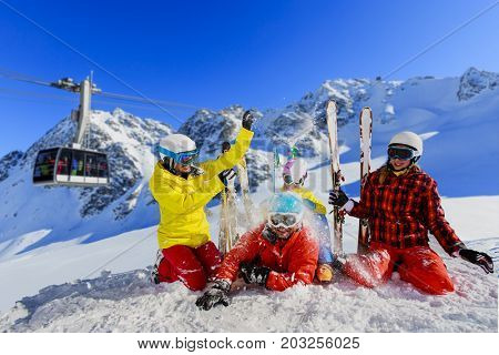 Happy family enjoying winter vacations in mountains . Ski, Sun, Snow and fun. Cable car, ski lift in background.