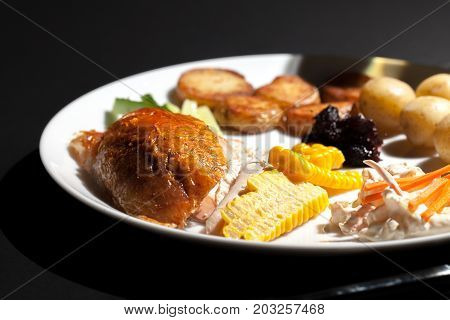Nutritional chicken dinner meal. Low calorie healthy food on a plate. Roast chicken with sweetcorn coleslaw cranberry sauce saute and boiled potatoes and cucumber.