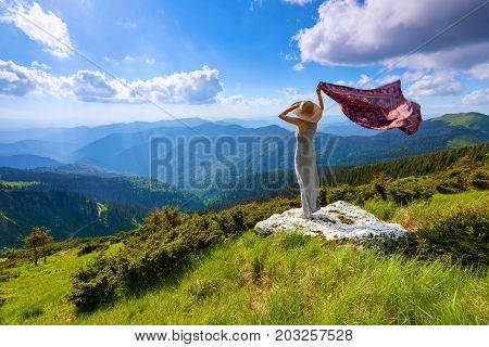 On the white rocks at the lawn the girl in long dress and hat is staying with the shawl in hand watching at the blue sky and mountains.