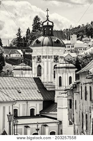 Church of the assumption Banska Stiavnica Slovak republic. Cultural heritage. Holy cross. Clock tower. Religious architecture. Black and white photo.