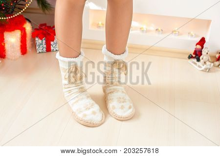 Young girl legs in cozy warm woolen ornamental socks with pompons on christmas background. Indoors horizontal image.
