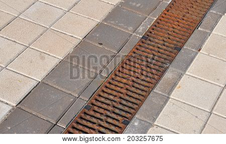 Gutter downspout pipe drain for roof runoff with  open water drainage in the pavement to repair.