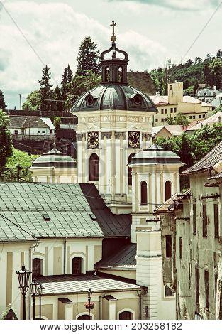 Church of the assumption Banska Stiavnica Slovak republic. Clock tower. Religious architecture. Old photo filter.