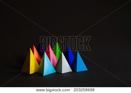 Minimalistic colorful composition abstract geometric shape figures on black background. Three-dimensional pyramid prism objects yellow blue pink green gray colored solid shapes.