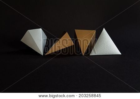 Gold silver minimalistic design geometric solid figures on black. Elegant prism pyramid triangle shape solid objects, paper background