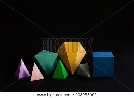 Colorful minimalistic composition abstract geometric solid figures on black background. Pyramid prism rectangular cube yellow blue pink green colored figures. shallow depth of field.