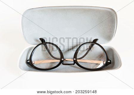 Stylish modern fashionable elegant black eyeglasses in white leather case. Indoors horizontal close-up image.