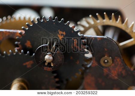 Rusty metal clock mechanism cog gears connection concept. Black iron wheels industrial still life photo. Macro view, selective focus