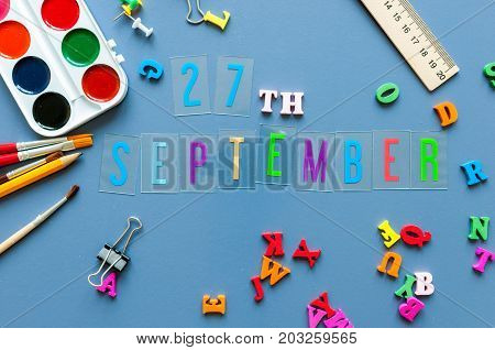 September 27th. Day 27 of month, Back to school concept. Calendar on teacher or student workplace background with school supplies on blue table. Autumn time.