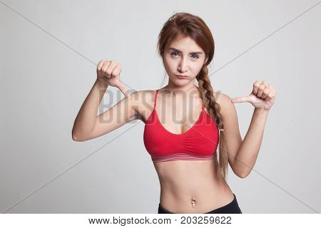 Unhappy Asian Girl In Sport Dresses Show Thumbs Down With Both Hands.