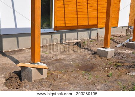 Wooden pillar on the construction site with screw and place for terrace. Wooden Pillars are structures that can be placed on Foundations or Platforms.