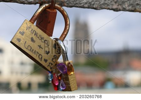 MAGDEBURG, GERMANY - SEPTEMBER 7, 2017: Love padlocks with blurred cathedral of Magdeburg in Background. (Magdeburg is the sister city of Nashville, USA.)