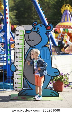 Restrictions on growth in a childrens amusement park, A five year old boy stands against the background of a mans growth line