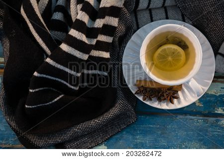 Overhead view of green tea by sweater on wooden table