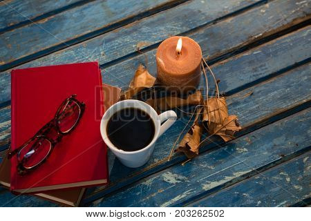 High angle view of tea cup with eyeglasses and books by illuminated candle on wooden table