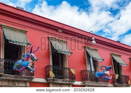 Red colonial building and artwork known as alebrije in Oaxaca Mexico