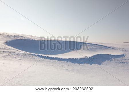 Golf bunker full of snow on the hill