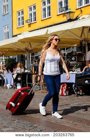 Copenhagen Denmark - August 24 2017: A woman with long blonde hair wearing a white sleeveless top blue jeans and white shoes draws a red wheeled suitcase through Nyhamn.