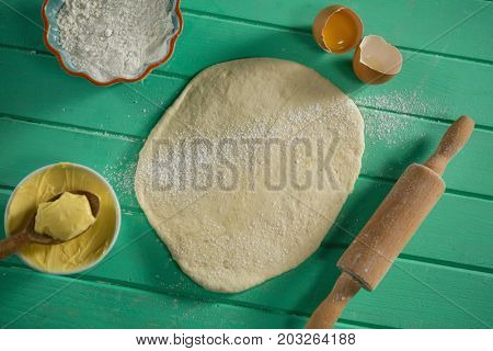 Overhead view of rolled dough by rolling pin and ingredients on table