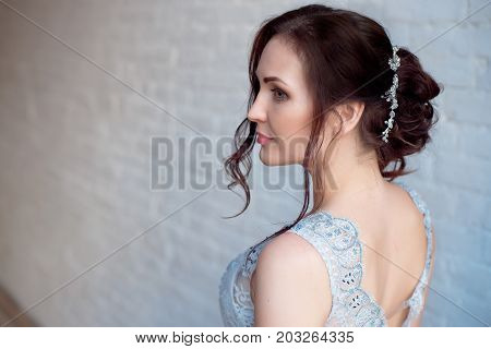Glamour lady portrait in luxury open back dress. Beautiful model girl with perfect fashion makeup and hairstyle. Female Elegant wedding hairstyle.