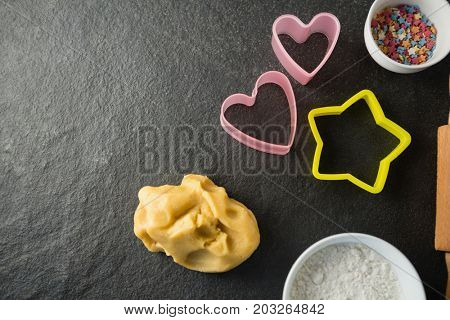 Overhead view of moulds with candies in bowl and dough at table