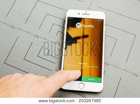 PARIS FRANCE - SEP 26 2016: Male hand holding New Apple iPhone 7 Plus after unboxing and testing by installing the app application software Spotify music welcome