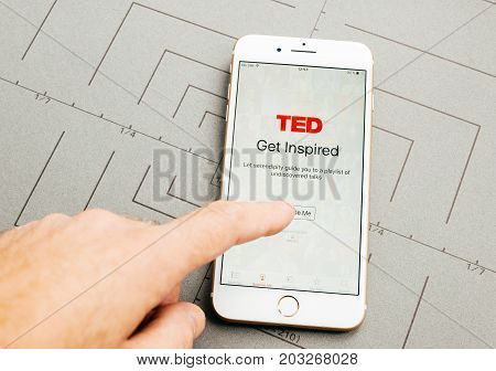 PARIS FRANCE - SEP 26 2016: Male hand holding New Apple iPhone 7 Plus after unboxing and testing by installing the app application software TED speaking media app