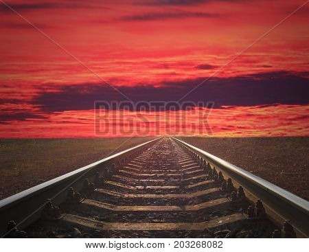 rails going away into the crimson sunset. rails going away into the dark landscape with fiery red sunset