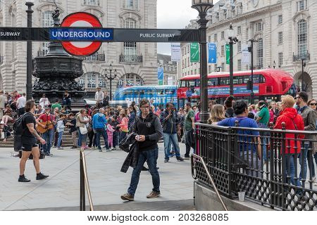 LONDON ENGLAND - JUNE 09 2017: Unknown people at Piccadilly Circus near entrance of London subway station London UK