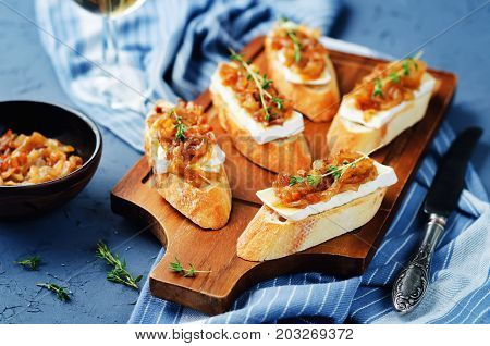 Bacon onion marmalade Brie crostini on a stone background