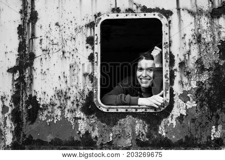 Black and white portrait of happy young woman in the window vintage train.