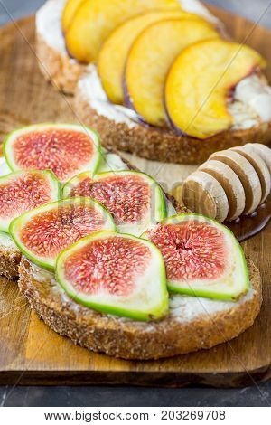 Healthy toasts or sandwiches with cream cheese ripe figs and peaches drizzled with honey. Wooden dipper. Top view close up.