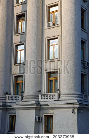 part of a gray building with columns and windows