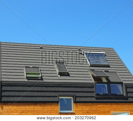 Energy saving concepts in new building energy efficiency roof design. Modern skylights dormers bitumen tiles and solar water panel heating.