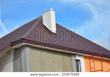 Construction or repair of the rural house with eaves windows chimney roofing fixing facade insulation plastering and painting walls. Painting House Facade Wall. Metal Tiled Roofing.
