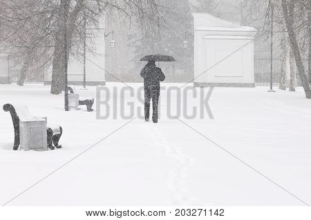 Bad weather in a city in winter: heavy snowfall and blizzard. Male pedestrian hiding from the snow under umbrella