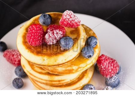 Powdered sugar coated raspberries and blueberries in syrup on top of pancakes stack