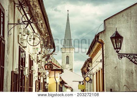 Hrnciarska street with Calvinist church in Kosice Slovak republic. Folk art theme. Religious architecture. Retro photo filter.