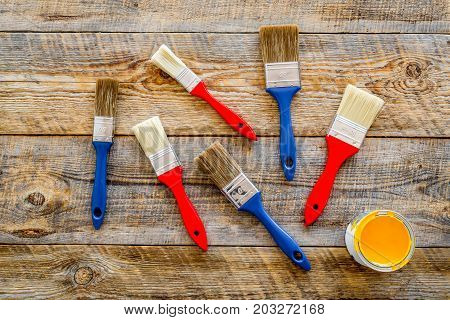 house-painter desk with set of building implements, pain, brushes on wooden desk background top view